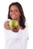 Junge glückliche indische Frau, die einen Apfel anhält stockfoto