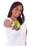 Junge glückliche indische Frau, die einen Apfel anhält stockfotos