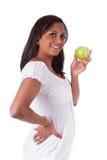 Junge glückliche indische Frau, die einen Apfel anhält Lizenzfreies Stockbild