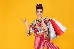 Junge glückliche kaukasische Frau in der zufälligen bunten Kleidung, die Taschen hält und über orange Hintergrund kauft lizenzfreies stockfoto