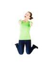 Junge glückliche kaukasische Frau, die in die Luft mit den Daumen oben springt lizenzfreies stockfoto