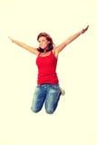Junge glückliche kaukasische Frau, die in die Luft springt Stockfotografie