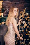 Junge glückliche lächelnde Frau in einem eleganten, schleichenden Goldabendkleid verziert einen Weihnachtsbaum mit einem Lächeln  stockfotos