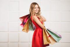 junge glückliche lächelnde Frau mit Einkaufstaschen Lizenzfreies Stockfoto
