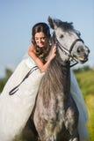 Junge glückliche lächelnde Frau mit Pferd Stockfotografie