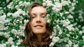 Junge glückliche lächelnde grünäugige Frau mit Blumen Natürliche Schönheit Stockfoto