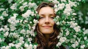 Junge glückliche lächelnde grünäugige Frau mit Blumen Natürliche Schönheit Stockfotos