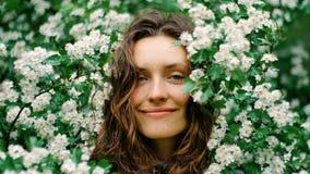 Junge glückliche lächelnde grünäugige Frau mit den Blumen, welche die Kamera betrachten Natürliche Schönheit Lizenzfreies Stockfoto