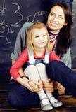 Junge glückliche lächelnde Mutter mit blonder Tochter im Klassenzimmer an der umarmenden Tafel, Lebensstilleutekonzept Stockbild