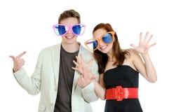 Junge glückliche lächelnde Paare, die großen farbigen Gläser haben Spaß tragen Stockfoto