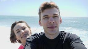 Junge glückliche lächelnde Paare notierende theirselves in einem selfie Modus auf dem felsigen Strand Starker Wind und Wellen stock video footage