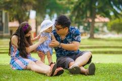 Junge glückliche liebevolle asiatische koreanische Elternpaare, die zusammen das süße Tochterbaby herein sitzt auf Gras am grünen stockfotografie