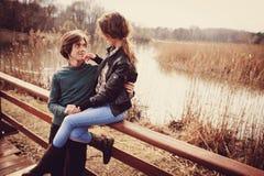 Junge glückliche liebevolle Paare, die Spaß auf dem Weg im Vorfrühling haben Lizenzfreies Stockfoto
