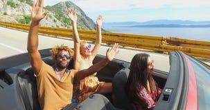 Junge glückliche Menschen an den Sommerferien, die den Spaß fährt im roten Kabriolett haben stock video footage