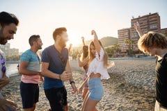Junge glückliche Menschen, die auf Strand tanzen stockfotografie