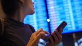 Junge glückliche Mischrasse-Mädchen-Prüfungs-Flugzeit unter Verwendung des Handys nahe Abfahrt-Brett im Flughafen 4K Slowmotion B stock video footage