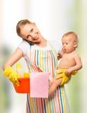 Junge glückliche Mutter ist eine Hausfrau mit einem Baby tut Hausarbeit und Stockbilder