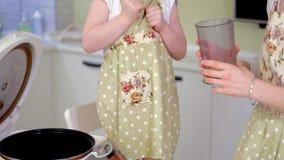 Junge glückliche Mutter und ihr nettes gelocktes Kleinkind daughterr in einer Küche zu kochen stock video footage