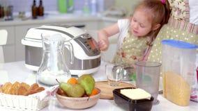 Junge glückliche Mutter und ihr nettes gelocktes Kleinkind daughterr in einer Küche zu kochen stock footage