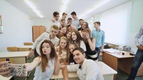 Junge glückliche nette Studenten, die selfie in der Schulklasse machen stock video footage