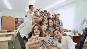 Junge glückliche nette Studenten, die selfie in der Schulklasse machen stock footage