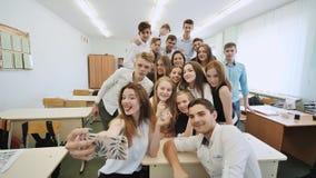 Junge glückliche nette Studenten, die selfie in der Schulklasse machen stockbilder