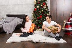 Junge glückliche Paare in den Pyjamas freuen sich an ihren Geschenken während sitt Lizenzfreie Stockfotografie