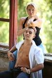 Junge glückliche Paare, die am Fenster sitzen stockfotografie