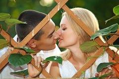 Junge glückliche Paare, die am hölzernen Gitter küssen Stockfotos