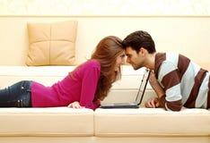 Junge glückliche Paare, die an Laptop arbeiten stockbild