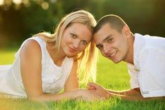 Junge glückliche Paare, die sich auf Gras hinlegen Lizenzfreie Stockfotos