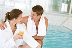 Junge glückliche Paare entspannen sich am Swimmingpool Stockfotografie