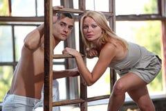 Junge glückliche Paare am geöffneten Fenster Stockfotos