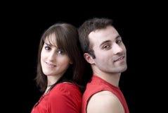 Junge glückliche Paare im Rot gegen Schwarzes lizenzfreie stockfotos