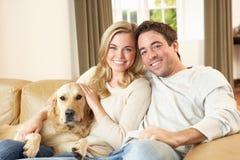 Junge glückliche Paare mit dem Hund, der auf Sofa sitzt Lizenzfreie Stockfotos