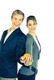 Junge glückliche Paare mit Orange Lizenzfreie Stockbilder