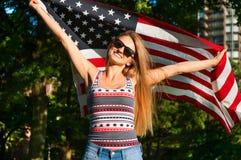 Junge glückliche Patriotfrau, welche die Flagge Vereinigter Staaten hält Stockfotos