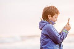 Junge glückliche preeteen den Jungen, der smth auf Telefonschirm, outdoo betrachtet stockfoto