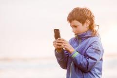 Junge glückliche preeteen den Jungen, der smth auf Telefonschirm, outdoo betrachtet stockbild