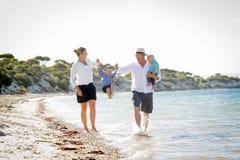 Junge glückliche schöne Familie, die zusammen auf den Strand genießt Sommerferien geht Stockfotografie