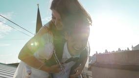 Junge glückliche schöne Paare auf dem Dach die Braut springt auf der Rückseite des Bräutigams stock video