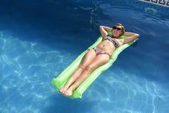 Junge glückliche Schönheit, beim Bikini- und Sonnenbrillelügen entspannen sich auf Flossluftmatratze am Ferienhotelerholungsort-S Lizenzfreies Stockfoto