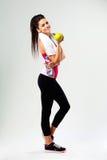 Junge glückliche Sportfrau mit Apfel und Flasche Wasser Lizenzfreie Stockfotografie