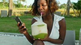 Junge glückliche und attraktive schwarze afroe-amerikanisch Frau unter Verwendung des Internet-Social Media am Handy am tropische stock video footage