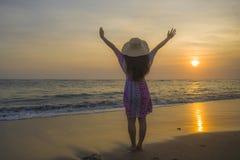 Junge glückliche und entspannte Frau im Sommerhut, der die Sonne über dem Meer während eines erstaunlichen schönen Sonnenuntergan lizenzfreies stockfoto