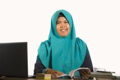 Junge glückliche und erfolgreiche moslemische Studentenfrau in der traditionellen Islam hijab Kopftuchfunktion auf Schreibtisch s stockfoto