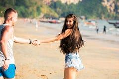 Junge glückliche und frohe kaukasische erwachsene romantische Paare, die zusammen während Händchenhalten in der Sommerkleidung au stockfotografie
