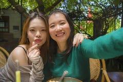 Junge glückliche und nette asiatische chinesische Freundinnen, die selfie Porträtphoto mit Handykamera für die Anwendung auf Inte stockfoto