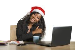 Junge glückliche und schöne schwarze afroe-amerikanisch Geschäftsfrau in der Santa Christmas-Hutfunktion an Bürocomputertisch läc stockbild