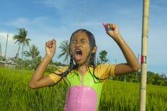 Junge glückliche und sorglose schöne alte Freien des Kind 7 oder 8 Jahre, die Dusche an einer schönen Reisterrasse spielerisch un stockfotos